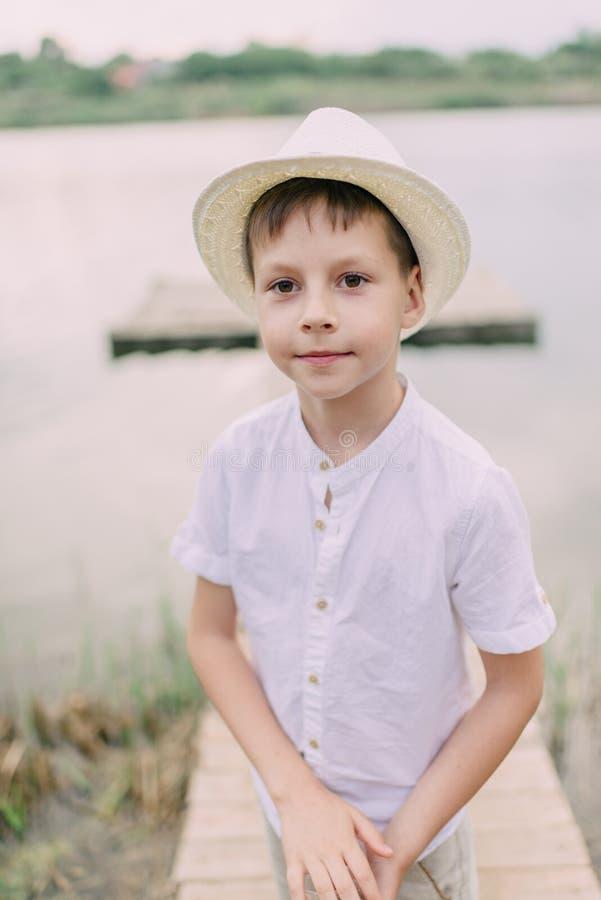 Pojke i hatt nära floden arkivfoto