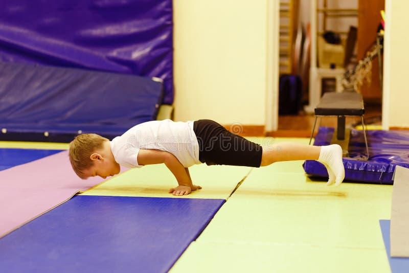 Pojke i likformign som gör handstans Yoga för barn` s Övningskrokodil royaltyfri foto