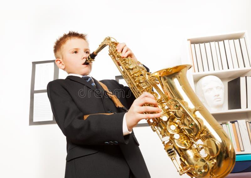 Pojke i skolalikformign som spelar på den alt- saxofonen fotografering för bildbyråer