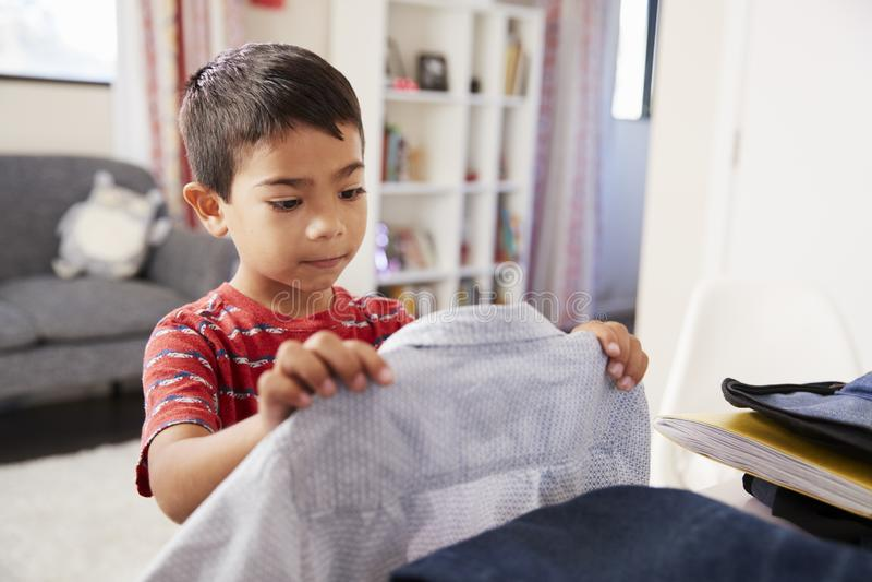 Pojke i sovrummet som väljer den skolmogna skjortan arkivbilder