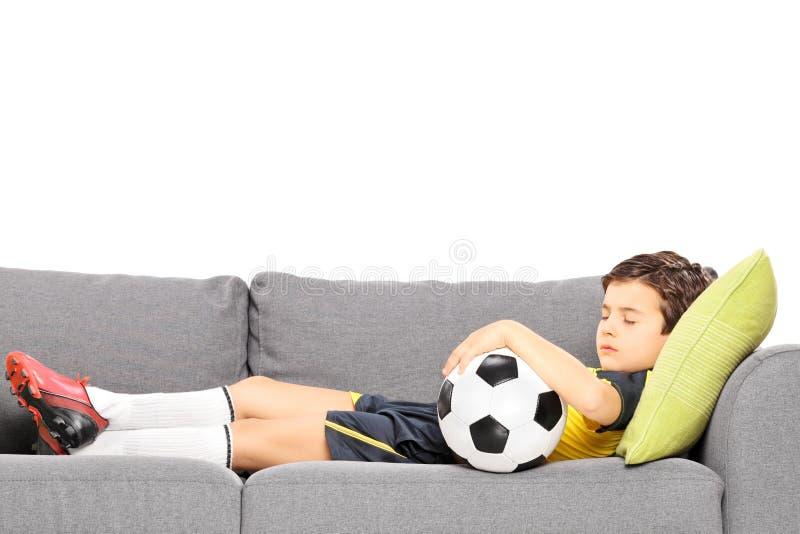 Pojke i sportswear med en fotboll som sover på en modern soffa royaltyfri foto