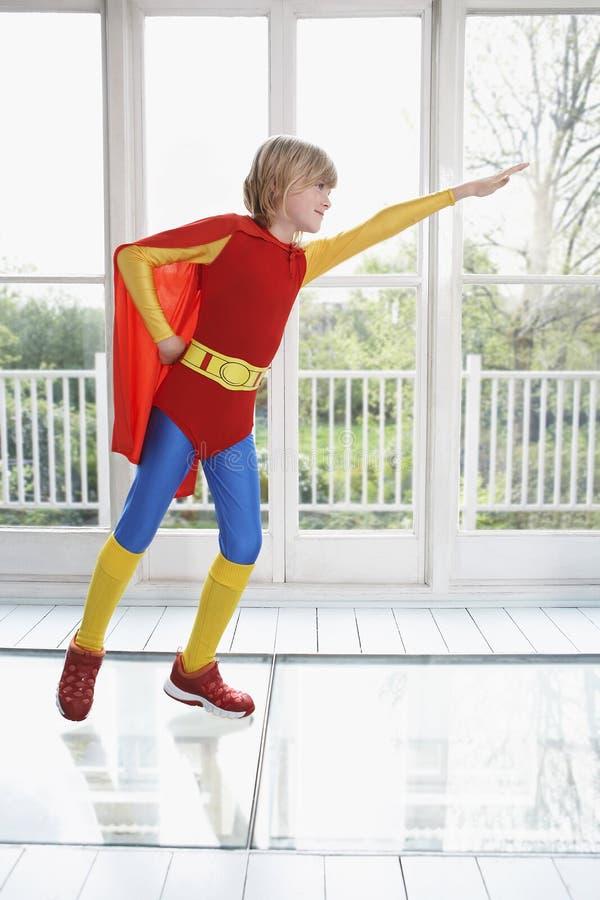 Pojke i Superherodräkt med den fördjupade armen arkivbilder