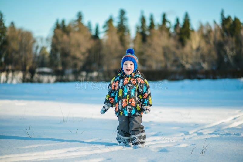 Pojke i vinteranseendet i snön arkivfoto