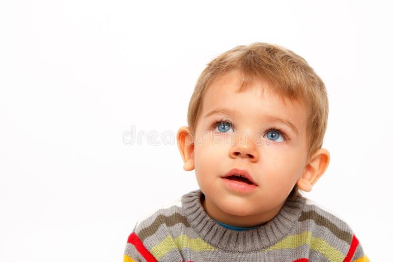 Pojke i vinterkläder som ser upp förbluffad royaltyfri bild