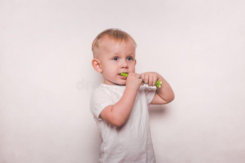 Pojke i vit som borstar hans tänder med en tandborste royaltyfri fotografi