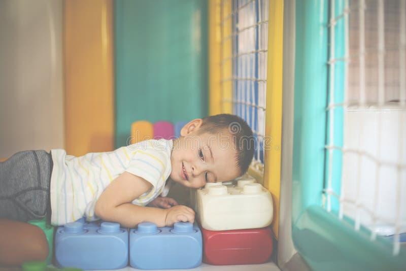 pojke little lekplats Pojke som ligger på kuber arkivbilder