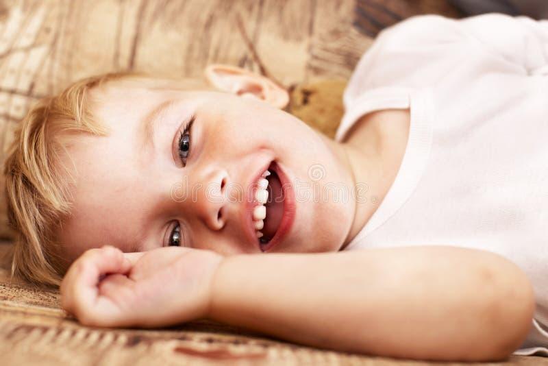 pojke little liggande sofa fotografering för bildbyråer