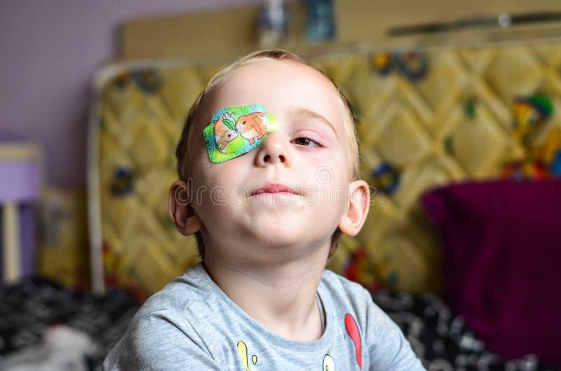 Pojke med ögonlapp fotografering för bildbyråer