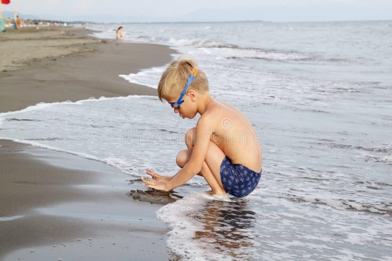 pojke med blont h?r, i att simma exponeringsglas som in spelar p? stranden arkivbilder
