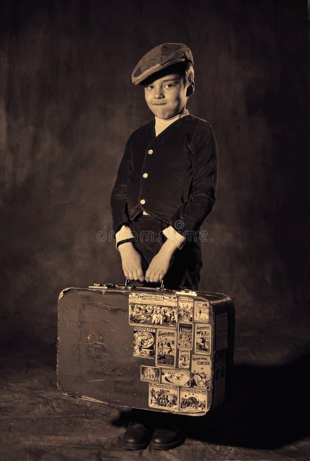 Pojke med den gamla resväskan arkivfoto