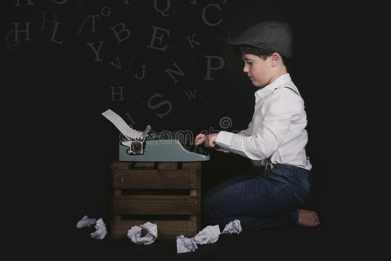 Pojke med den gamla skrivmaskinen royaltyfri fotografi