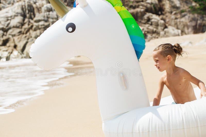 Pojke med den uppblåsbara enhörningen på stranden royaltyfria bilder