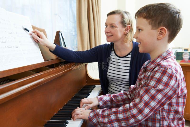 Pojke med det Having Lesson At för musiklärare pianot arkivfoto