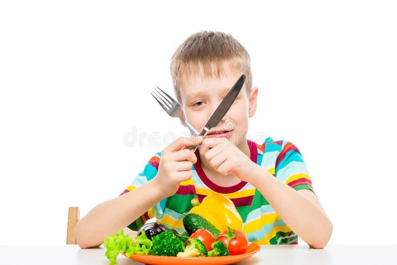 pojke med en kniv och en gaffel som ?ter nya r? gr?nsaker royaltyfri foto