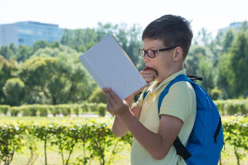 Pojke med en portfölj som läser en bok och biter ett äpple på gatan arkivbilder