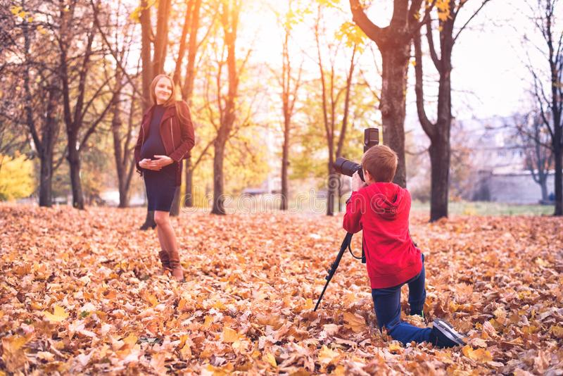 Pojke med en stor reflexkamera på en tripod Fotografier en gravid kvinna Familjfotoperiod arkivfoto