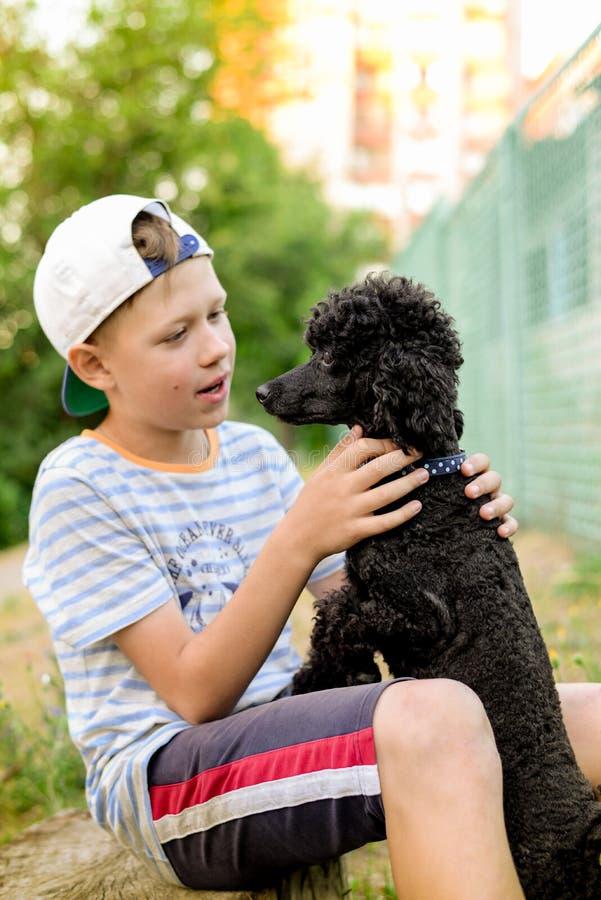 Pojke med en svart pudel arkivfoton