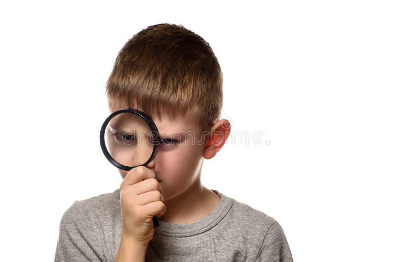 Pojke med ett förstoringsglas i hans händer utforskare little Vit bakgrund royaltyfria bilder