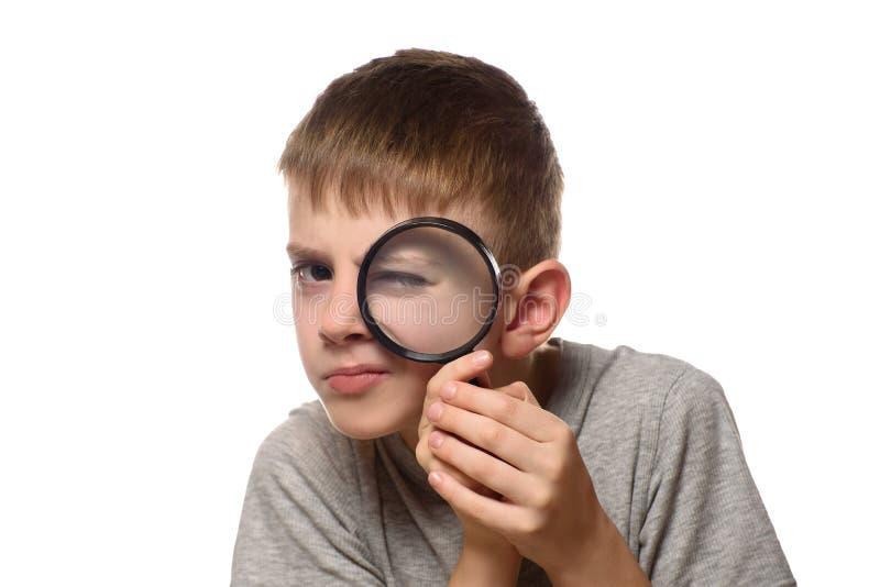 Pojke med ett förstoringsglas i hans händer utforskare little Vit bakgrund royaltyfri fotografi
