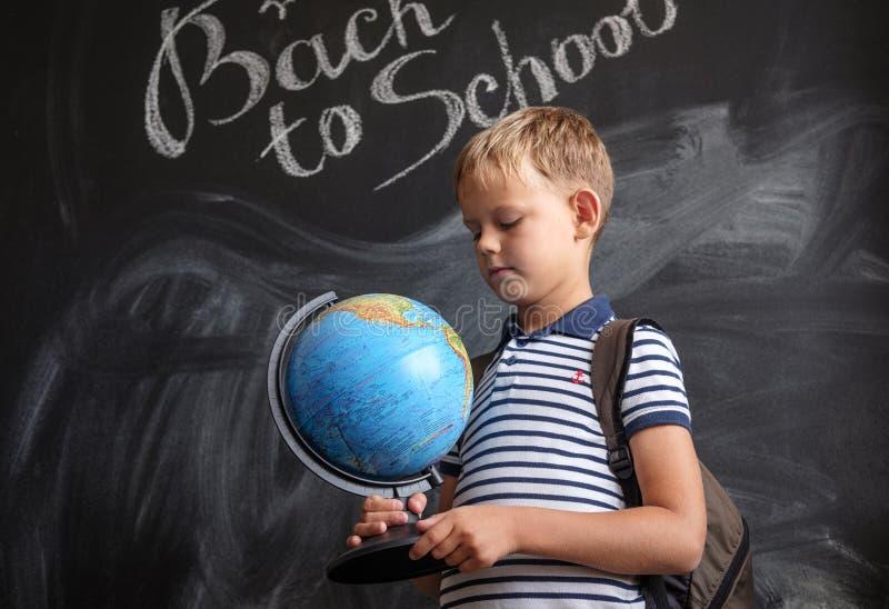 Pojke med ett jordklot på bakgrunden av skolförvaltningen arkivfoto