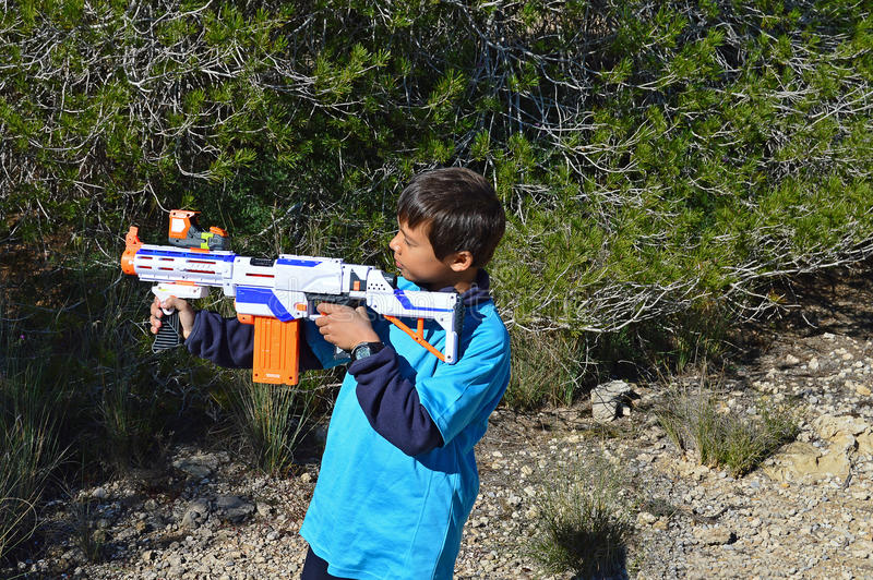 Pojke med ett plast- gevär fotografering för bildbyråer