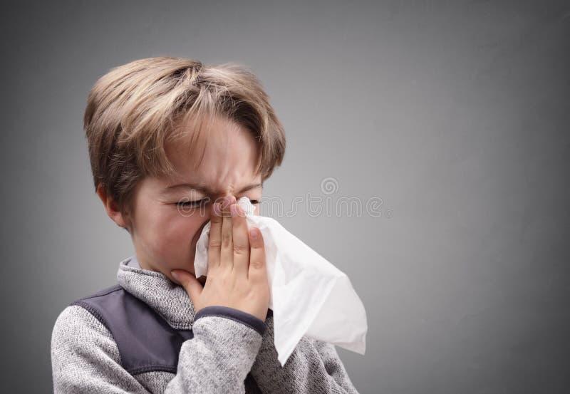 Pojke med ett silkespapper som blåser hans näsa fotografering för bildbyråer