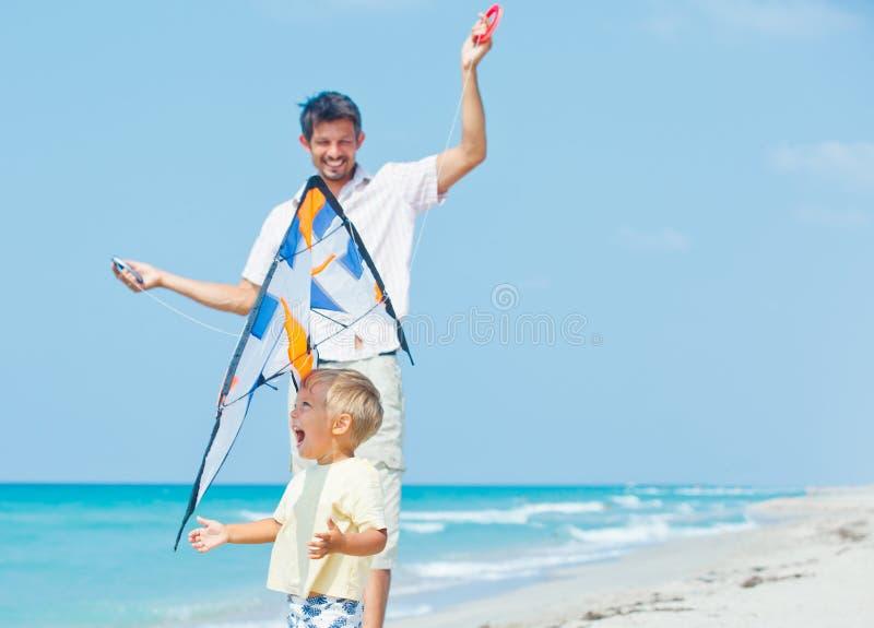 Pojke med fadern på stranden som leker med en drake royaltyfri foto