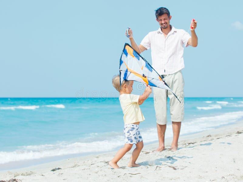 Pojke med fadern på stranden som leker med en drake royaltyfria bilder