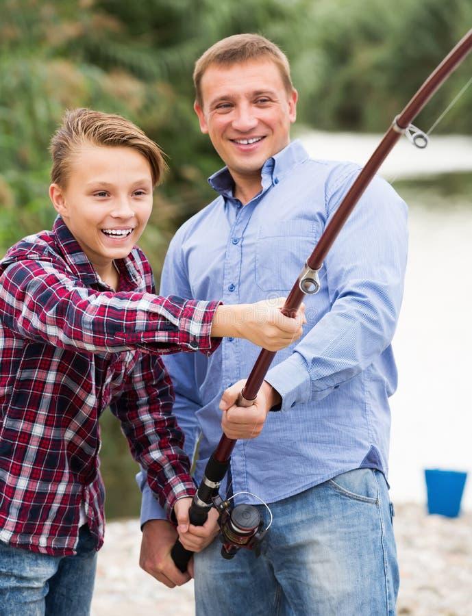 Pojke med fadern som tillsammans fiskar på den sötvattens- sjön fotografering för bildbyråer