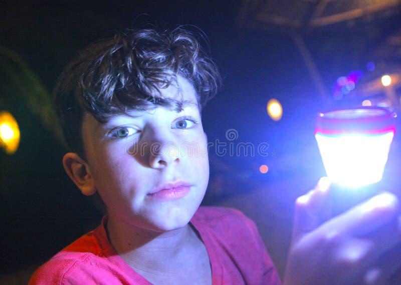 Pojke med ficklampan på natt royaltyfri foto