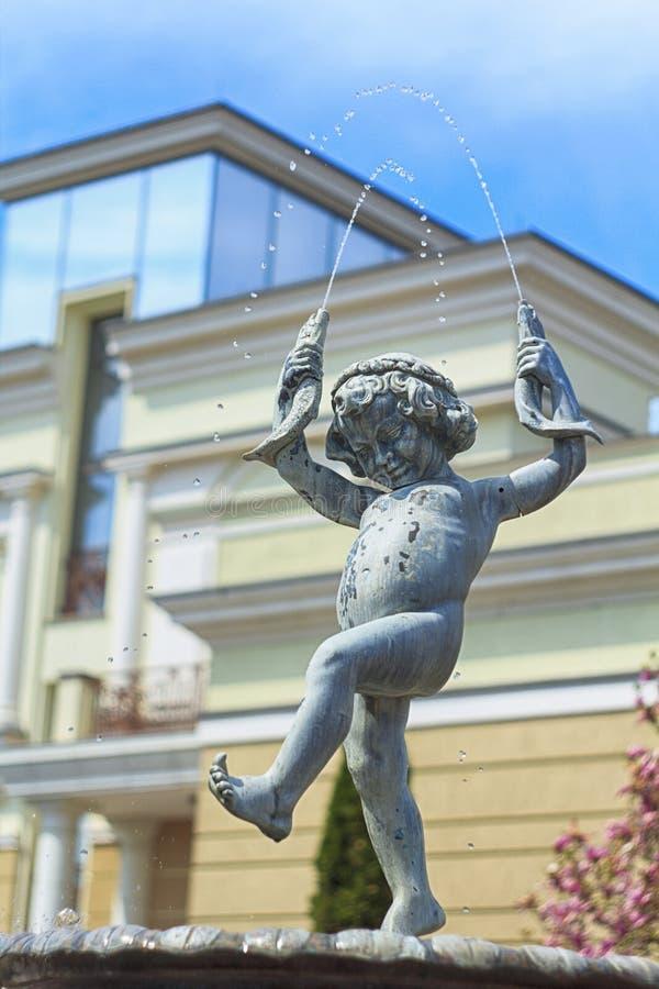 Pojke med fiskspringbrunnen royaltyfria bilder