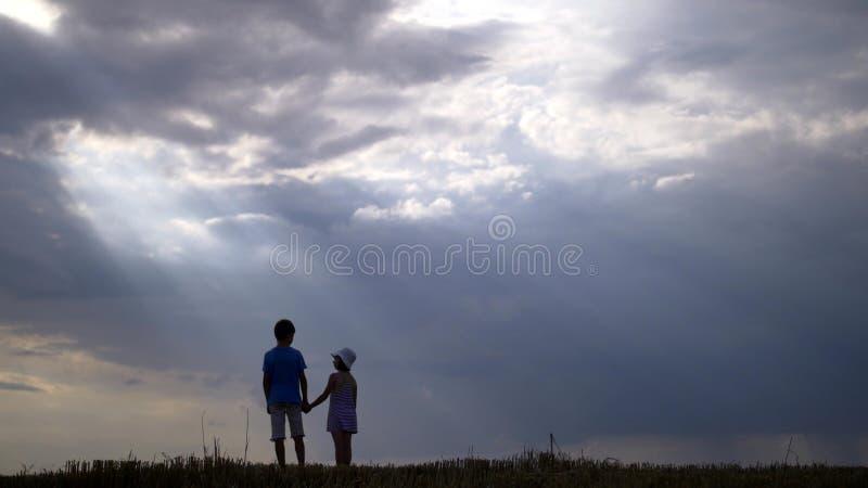 Pojke med flickan som går på en bakgrund av härliga moln i aftonen arkivbild