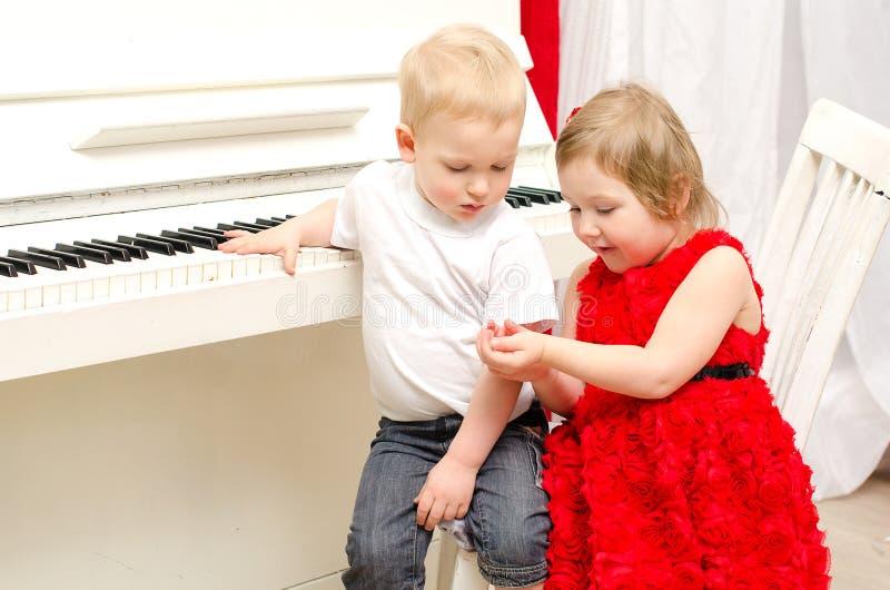 Download Pojke Med Flickan Som Sitter Nära Det Vita Pianot Arkivfoto - Bild av folk, piano: 37346780