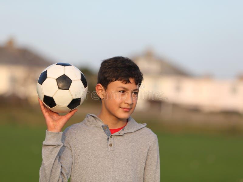 Pojke med fotbollbollen utanför arkivfoton