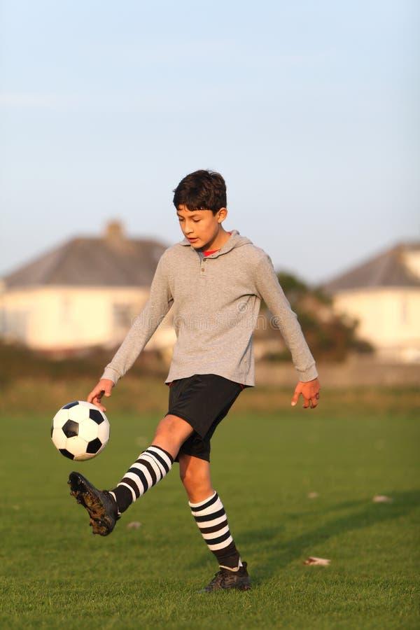Pojke med fotbollbollen utanför arkivfoto
