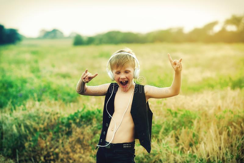 Pojke med hörlurar som lyssnar till musik i natur arkivbild