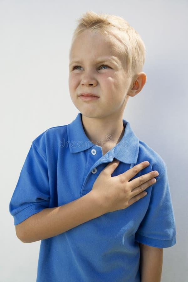Pojke med handen på hjärta arkivbild