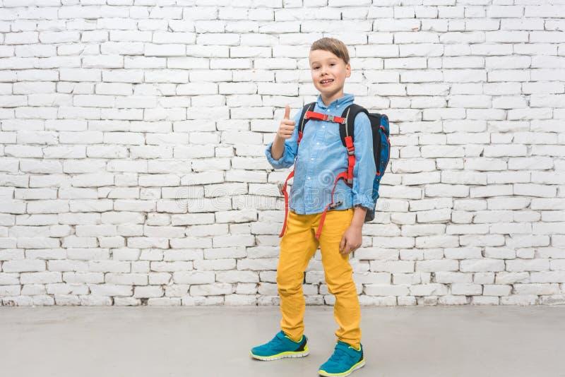 Pojke med hans ryggsäck som går till skolan arkivfoto