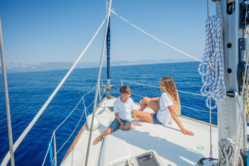 Pojke med hans syster ombord av seglingyachten p? sommarkryssning fotografering för bildbyråer