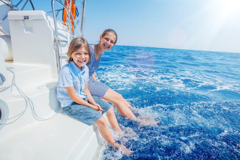 Pojke med hans syster ombord av seglingyachten p? sommarkryssning arkivfoton