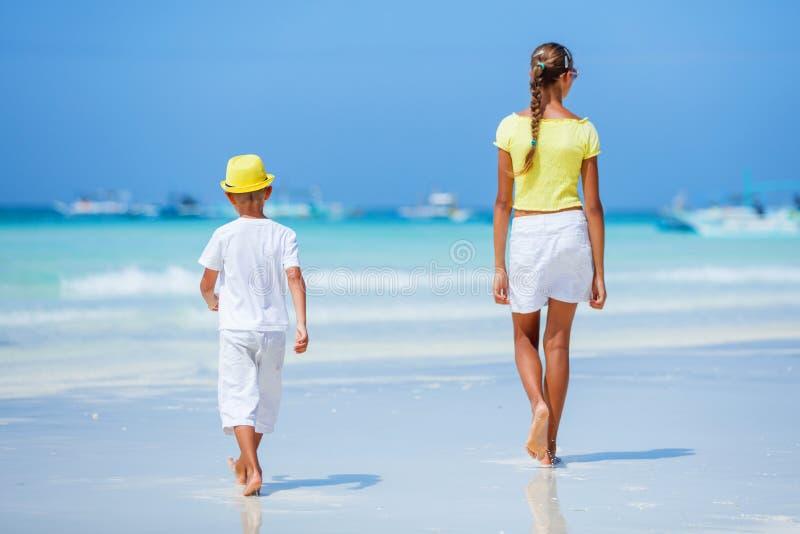 Pojke med hans syster som går på den tropiska havstranden Unge under familjhavssemester royaltyfria foton