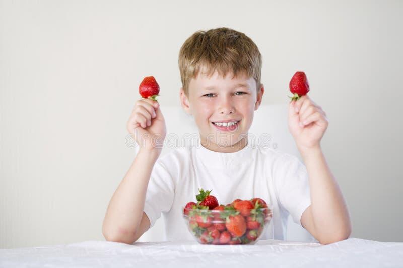 Pojke med jordgubbar royaltyfria foton