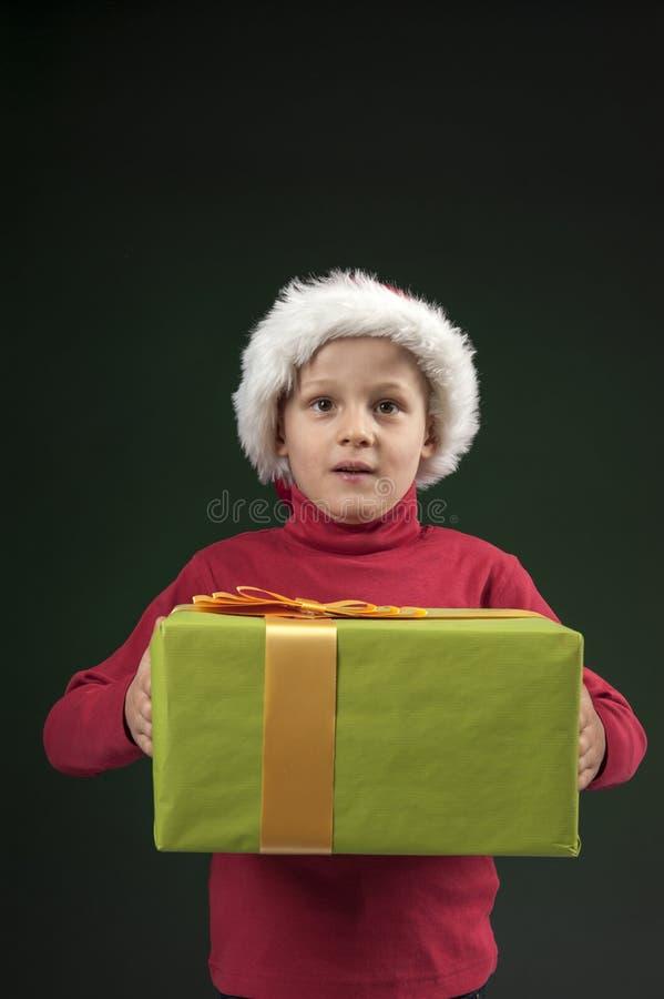 Pojke med jul hatt och present på dark - green royaltyfri fotografi