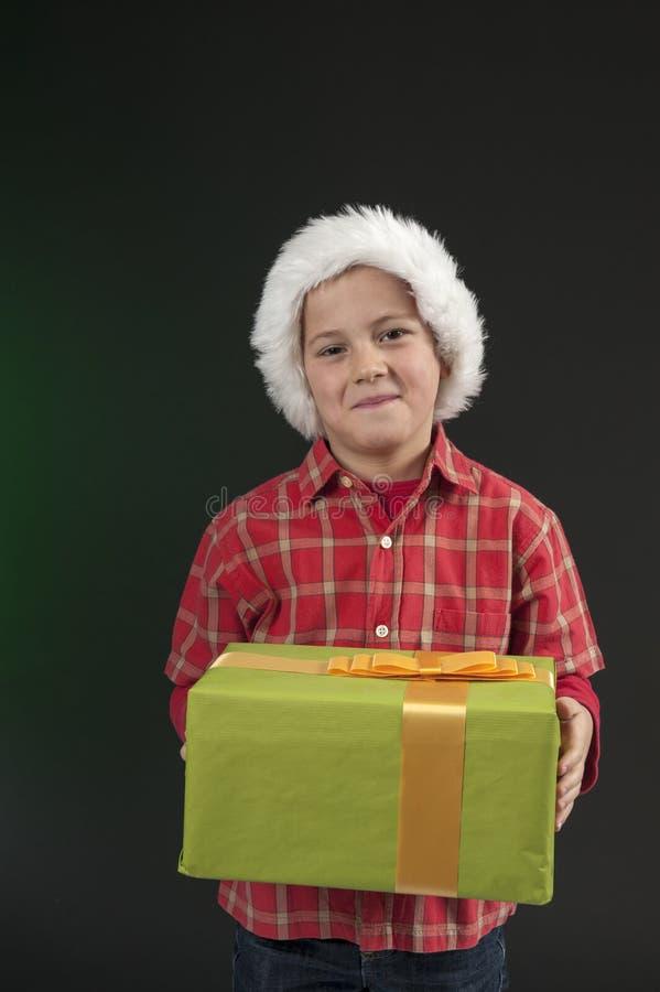 Pojke med jul hatt och present på dark - green arkivfoton
