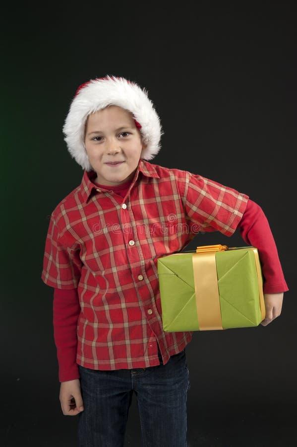 Pojke med jul hatt och present på dark - green arkivbilder