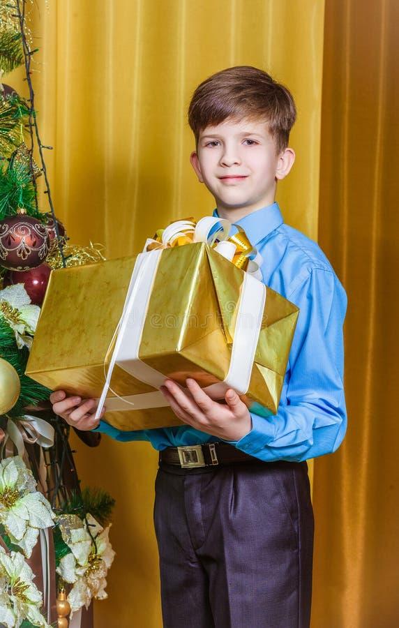 Pojke med julgåvan arkivfoto