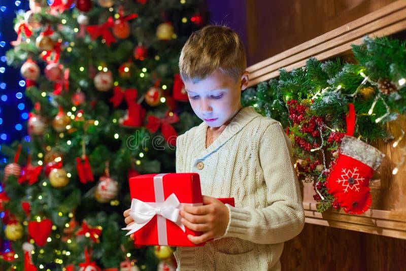 Pojke med julklapp för julgåvaöppning i Front Of Tr arkivfoto