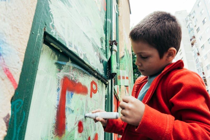 Pojke med markörteckningsgrafitti fotografering för bildbyråer