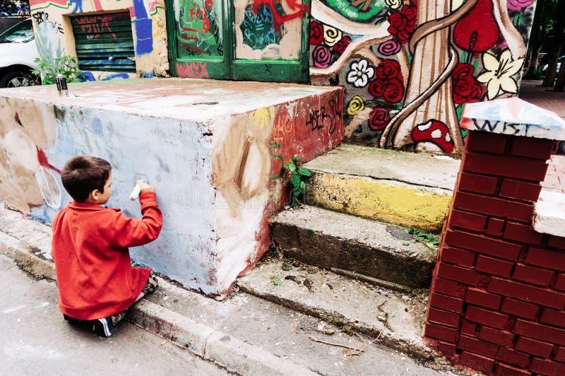 Pojke med markörteckningsgrafitti arkivbild