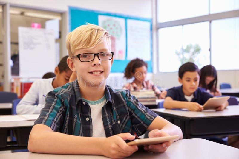 Pojke med minnestavlan i grundskolagrupp, stående arkivfoton